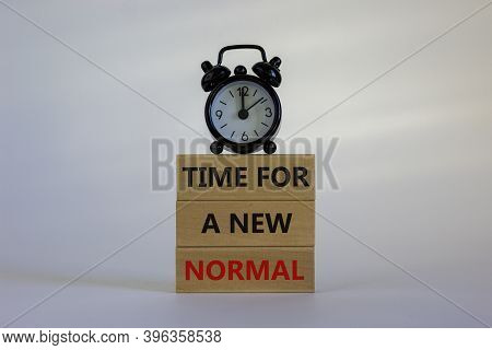 Time For A New Normal. Wooden Blocks With Words 'time For A New Normal'. White Table. Black Alarm Cl