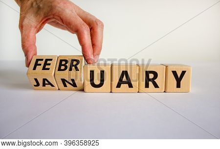 Symbol For The Change From January To February. Male Hand Flips Wooden Cubes And Changes The Inscrip