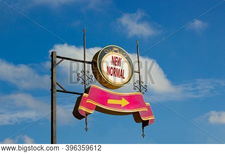 Time For A New Normal. Street Sign With Text 'new Normal' And Arrow On Metal Pole. Blue Sky Backgrou