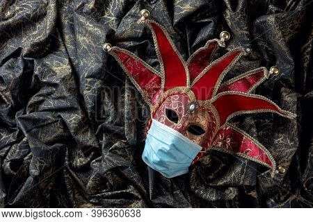 Carnival Mask In Protecting Mask. Conceptual Image Of The Theme Of The Virus. Copy Space.
