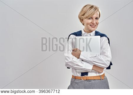 Portrait Of Elegant Middle Aged Caucasian Woman Wearing Business Attire Holding Laptop, Smiling At C