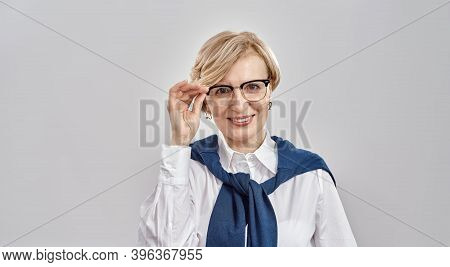 Portrait Of Elegant Middle Aged Caucasian Woman Wearing Business Attire Adjusting Her Glasses, Smili