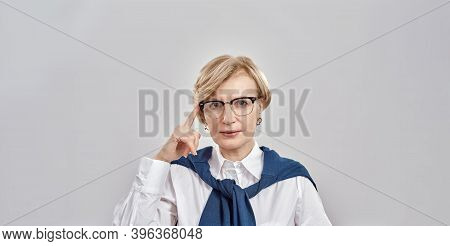 Portrait Of Elegant Middle Aged Caucasian Woman Wearing Business Attire Touching Her Glasses With On