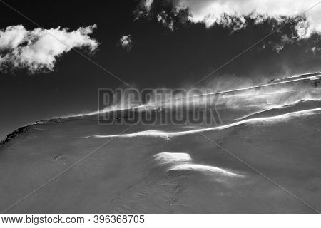 Off-piste Slope During Blizzard And Sunlit Sky With Clouds In Evening. Black And White Toned Landsca