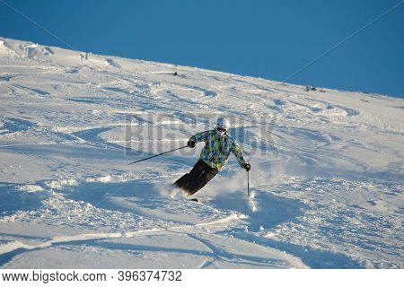 Les Orres, France - Circa 2015: Young skier coming down fast in fresh powder snow off-piste.