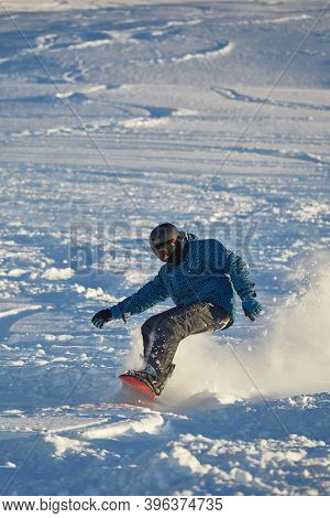 LES ORRES, FRANCE - CIRCA 2015: Young snowboarder coming down fast in fresh powder snow off-piste free ride.