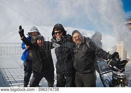 Les Orres, France - Circa 2015: Happy skiers posing for group photos while someone blasting snow on them using snow plowing machine to clear the terrace. People having fun