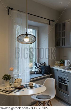 Kitchen Interior. In The Foreground - A Table With Two Coffee Cups, A Chair And A Lamp Above Them. I