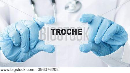 Doctor's Hands In Blue Gloves Shows The Word Troche. Medical Concept.