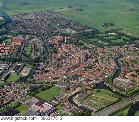 Bolsward, Holland, July 12 - 1990: Historical aerial photo of the city Bolsward with the townhall in the center, in the Dutch province Friesland
