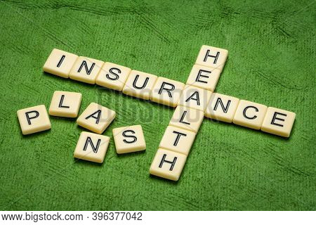 health insurance plans crossword in ivory letter tiles against textured handmade paper, healthcare concept