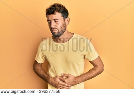 Handsome man with beard wearing casual yellow tshirt over yellow background with hand on stomach because indigestion, painful illness feeling unwell. ache concept.