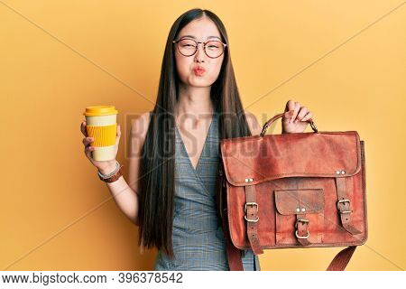 Young chinese woman holding leather bag and drinking a take away coffee puffing cheeks with funny face. mouth inflated with air, catching air.