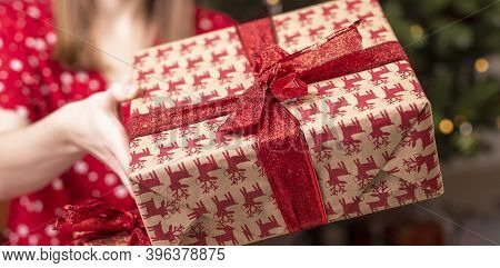Cropped Caucasuian Woman Holding Or Showing Christams Present Wrapped In Paper With Red Ribbon And B