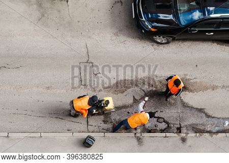 Road Workers In Orange Vests Repair The Road. Pit Removal And Patching. View From Above. Works Of Re