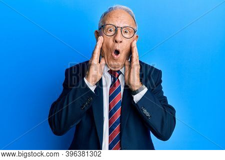 Senior caucasian man wearing business suit and tie afraid and shocked, surprise and amazed expression with hands on face
