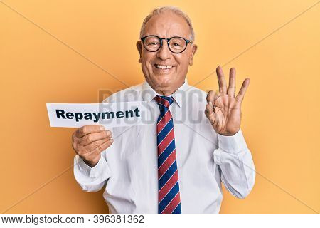 Senior caucasian man holding repayment word paper doing ok sign with fingers, smiling friendly gesturing excellent symbol