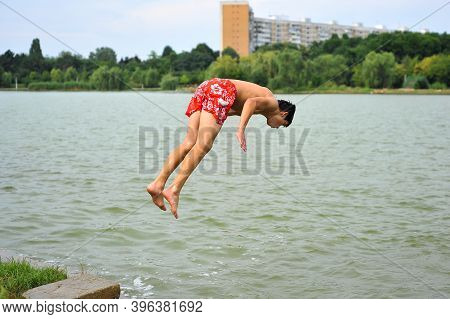 Bucharest, Romania - July 18, 2010: Teenage Boy Jumps Into The Water Of A Lake In A Public Park Duri