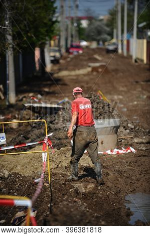 Bucharest, Romania - April 21, 2010: Man Working On The Sewer And Water Pipeline On An Unpaved Road