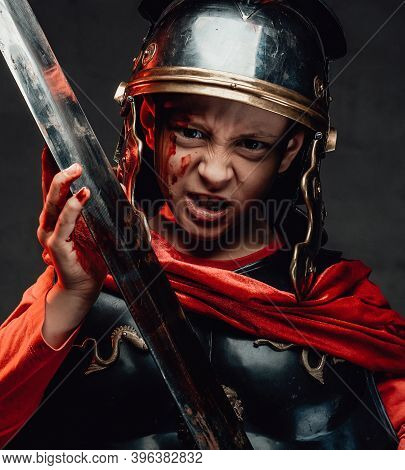 Fashion Of Mad And Savage Little Legionary Dressed In Dark Armour With Red Cape Holding A Sword In D