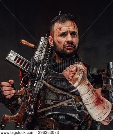 Holding Shotgun And Dressed In Dark Armour Stalker With Beard And Blood On His Face Poses In Dark Ba