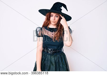 Young beautiful woman wearing witch halloween costume pointing unhappy to pimple on forehead, ugly infection of blackhead. acne and skin problem
