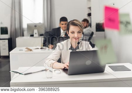 A Call Center Employee Sits At A Desk In The Office Of A Large Financial Company In A Strict Office