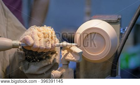 Professional Man Carpenter Holding Skew Chisel, Shaping Piece Of Wood And Using Wood Turning Lathe A