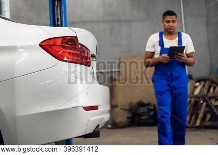 A Workshop Worker In Overalls Inspects A Car In A Workshop