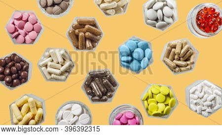 Medical Capsules And Pills In Hexagonal Jars On Yellow Background
