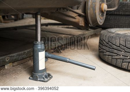 Car On Tire Mounting With Removed Wheel On Pneumatic Jack. Seasonal Tire Change. Vehicle Repair In A