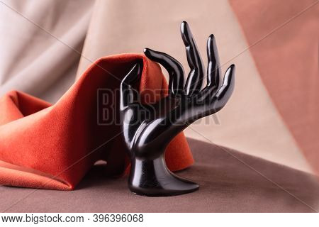 Black Plastic Mannequins Hand Holding Piece Of Velour Fabric. Fabric Texture Background