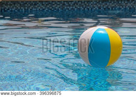 Beach Ball In Pool. Colorful Inflatable Ball Floating In Swimming Pool, Summer Vacation Concept.