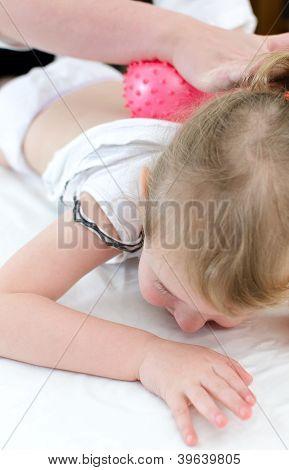 Masseuse Doing Massage To Little Girl Using A Ball