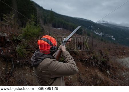 A Mean Wearing A Jacket, Blaze Orange Hat And Ear Protection Holds An Old Double Barrel Shotgun, Aim