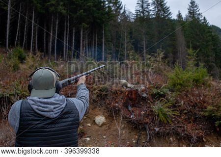 A Mean Wearing A Vest, Hat And Ear Protection Holds An Old 12 Gauge Shotgun, Aiming And Shooting At