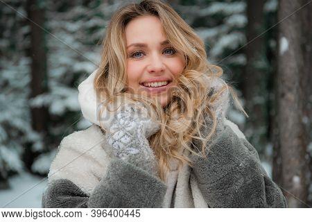 Close Up Portrait Of A Young Beautiful Smiling Blonde Woman In A Snowy Forest In Winter.