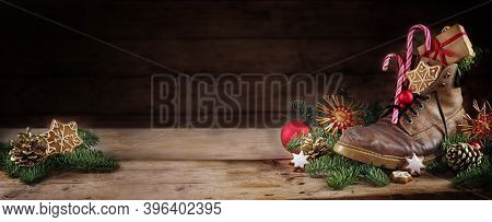 Old Hiking Boot Filled With Sweets, Gifts And Christmas Decoration, German Tradition On Nicholas Or