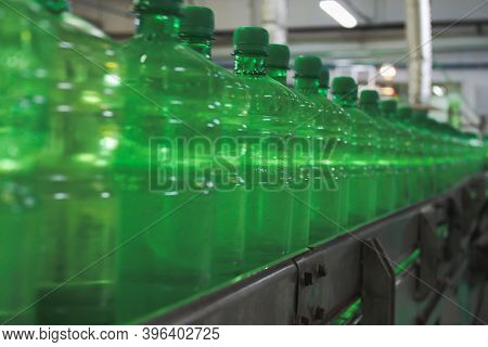 A Conveyer Belt With Green Plastic Bottles For Beverages. Perspective View. Concept Of Producing Cle