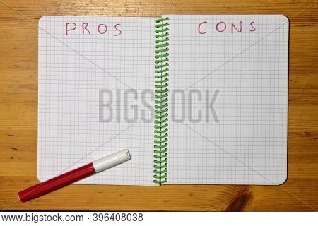 Pros Cons List In A Checkered Notebook And Red Marker. High Quality Photo