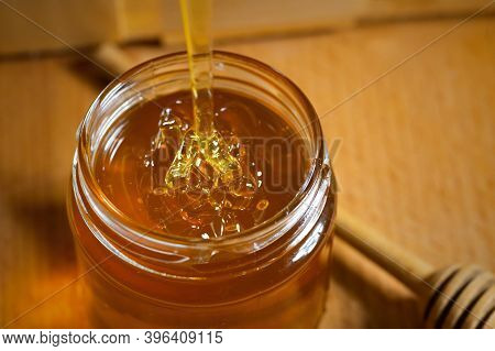 Pouring Aromatic Honey Into Jar, Closeup. A Glass Jar Of Honey And A Wooden Honey Dipper On A Wooden