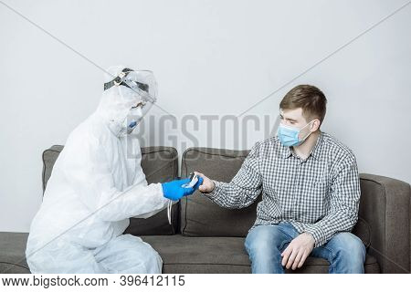 Doctor In Biohazard Suit And Mask Measuring Temperature Of Infected Asian Patient In Research Clinic