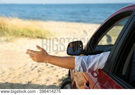 Man Waving From Car Window On Beach, Closeup. Summer Trip