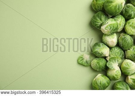 Fresh Brussels Sprouts On Green Background, Flat Lay. Space For Text