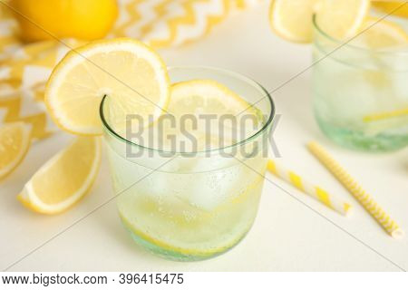 Soda Water With Lemon Slices And Ice Cubes On White Table