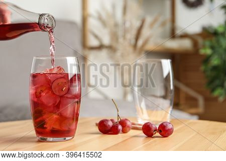 Pouring Grape Soda Water Into Glass On Wooden Table Indoors, Space For Text. Refreshing Drink