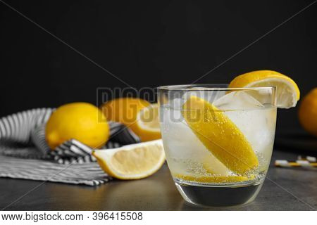 Soda Water With Lemon Slices And Ice Cubes On Grey Table. Space For Text