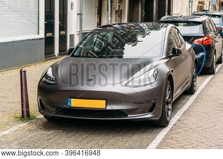 Amsterdam, Netherland - March 2020 : Tesla Modern Electric Car Is Parked At Charging Station On Stre