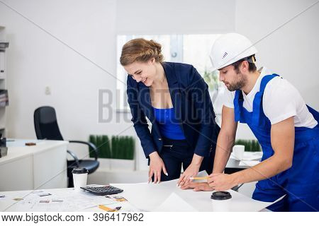 A Male And A Female Construction Engineer Working On Some Technical Drawings In The Office, Construc