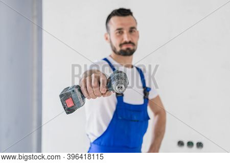 The Man Looks At The Camera And Shows The Drill